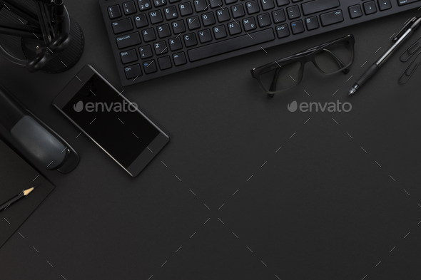 Top view of pitch black office desk with computer and supplies - Stock Photo - Images
