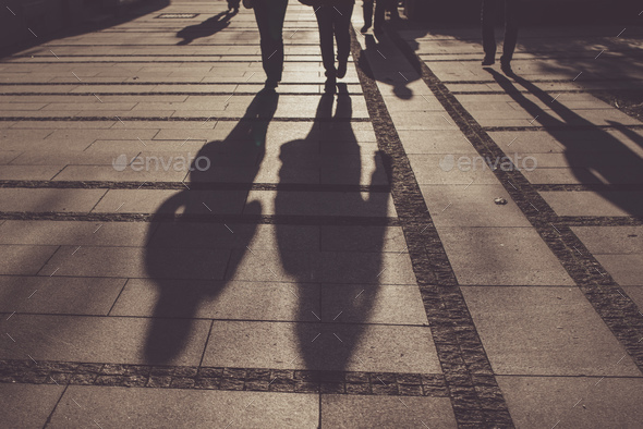 Silhouettes of people walking on city street - Stock Photo - Images