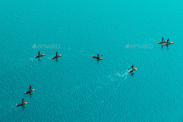 Aerial view of unrecognizable people stand up paddle boarding - Stock Photo - Images