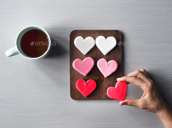 People Hands Showing Heart Shape Cookies with Coffee Cup - Stock Photo - Images