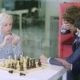 Two Young Businessmen Play Chess with a Cute Blonde and Lose - VideoHive Item for Sale
