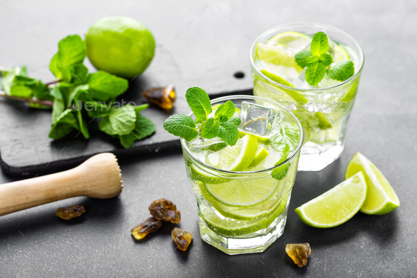 Summer mint lime refreshing cocktail mojito with rum and ice in glass on black background top view - Stock Photo - Images