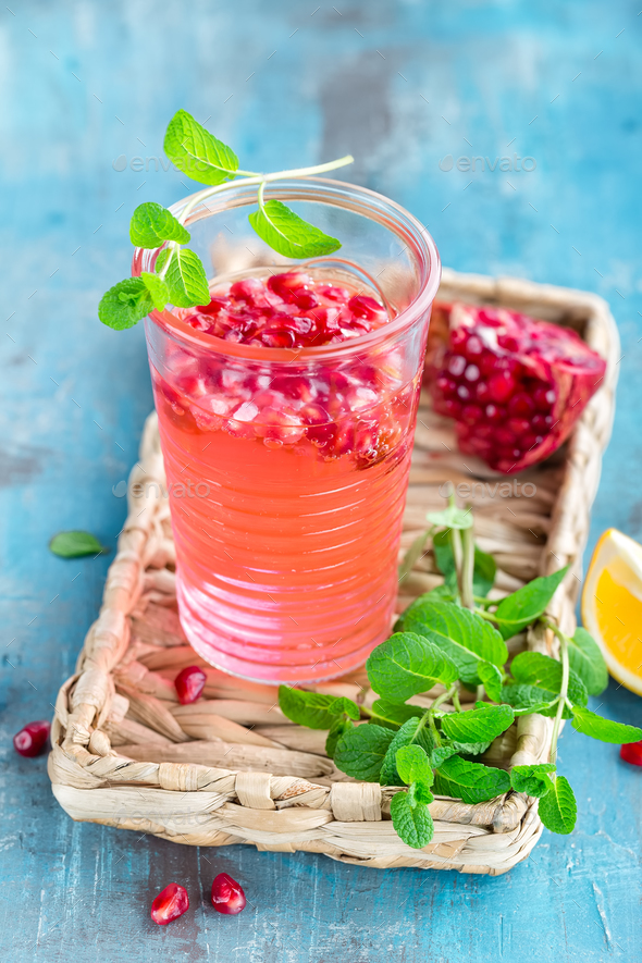 Infused pomegranate water with fresh lemon and ice, cold healthy refreshing and detox drink - Stock Photo - Images