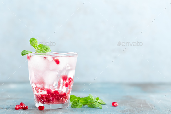 Infused water made of fresh pomegranate and mineral water with ice, cold refreshing and detox drink - Stock Photo - Images