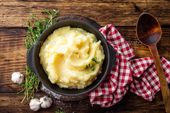 Mashed potatoes, boiled puree in cast iron pot on dark wooden rustic background, top view - Stock Photo - Images