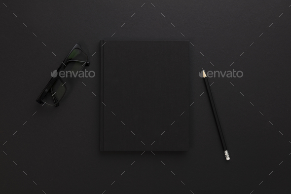 Top view of low key black office desk with notebook and supplies - Stock Photo - Images