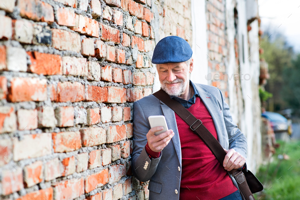 Senior man with smartphone against brick wall, texting. - Stock Photo - Images