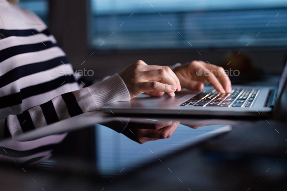 Unrecognizable woman sitting at desk working on laptop. - Stock Photo - Images