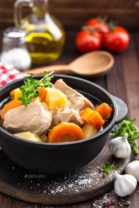 Meat stewed with carrots and potatoes in sauce on wooden rustic background - Stock Photo - Images