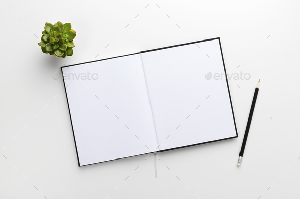 Top view of contemporary white office desk with book and pencil - Stock Photo - Images
