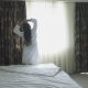 Beautiful Girl in a White Coat Goes To the Window in a Hotel Room - VideoHive Item for Sale