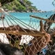 Man Swinging Relaxed in a Hammock on the Beach in Front of the Beautiful Blue Ocean. Hiding Him From - VideoHive Item for Sale