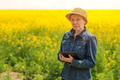 Female farmer using tablet computer in rapeseed field