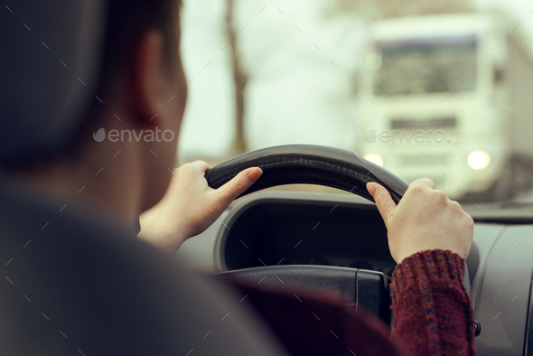 Woman driving car toward a large truck on the road - Stock Photo - Images