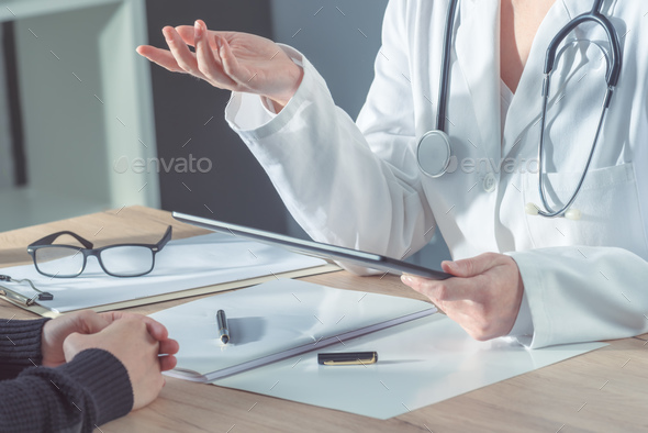 Doctor advising patient in hospital office - Stock Photo - Images