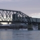 Tracking PAN of Railway Bridge Over the River at Dawn with Industrial Building in the Background.