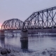 of Railway Bridge Over the River at Dawn with a Mountain Forest and Traffic Highway in the