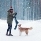 A Woman Playing with Her Dog and Scarf in Forest