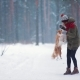 Young Woman Outdoors Training Cute Collie in Winter