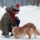 Young Woman Outdoors Playing with Dog in Winter