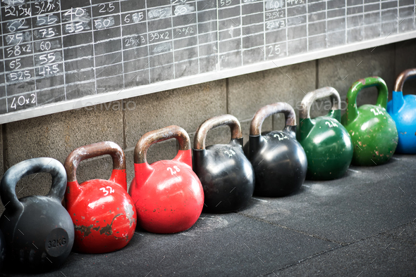 Row of colorful kettlebell weights in a gym - Stock Photo - Images