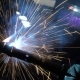 Welder Builds Up the Metal on the Workpiece. Sparks From Welding. Welding Mask