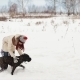 Mother and a Daughter Playing with a Dog in Winter