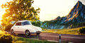 Cute little retro car goes by wonderful countryside road at sunset - PhotoDune Item for Sale