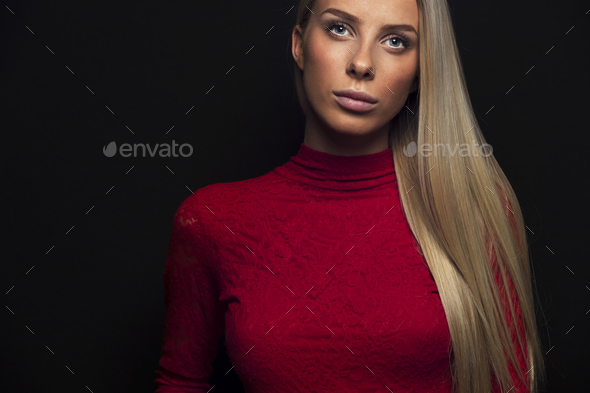 Dark portrait of a blonde woman in red dress - Stock Photo - Images
