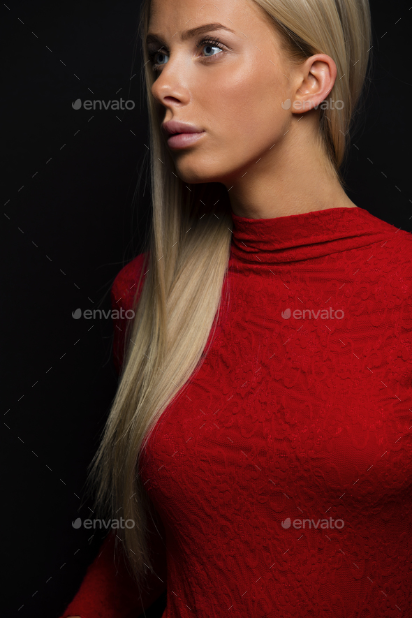 Dark portrait of a pretty blonde woman in red dress on black bakground - Stock Photo - Images