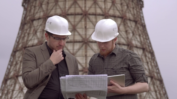 Two Businessmen in the Construction Helmets on the Background of the Nuclear Power Plant