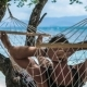 Man Swinging Relaxed in a Hammock on the Beach in Front of the Blue Ocean. Hiding Him From the Sun - VideoHive Item for Sale