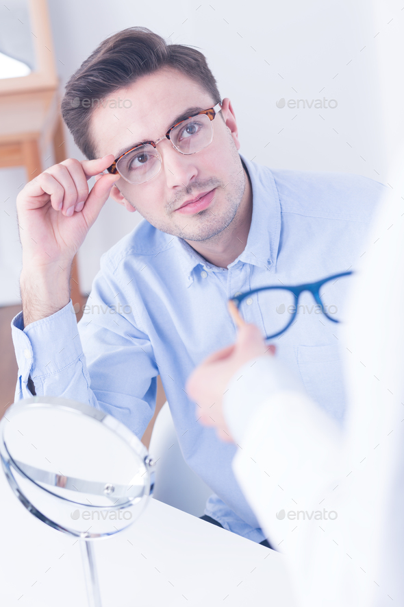 Man trying on new eyeglasses - Stock Photo - Images