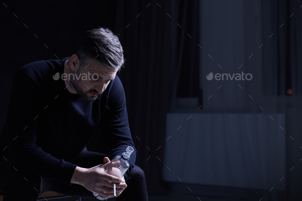 Man sitting and holding a bottle - Stock Photo - Images