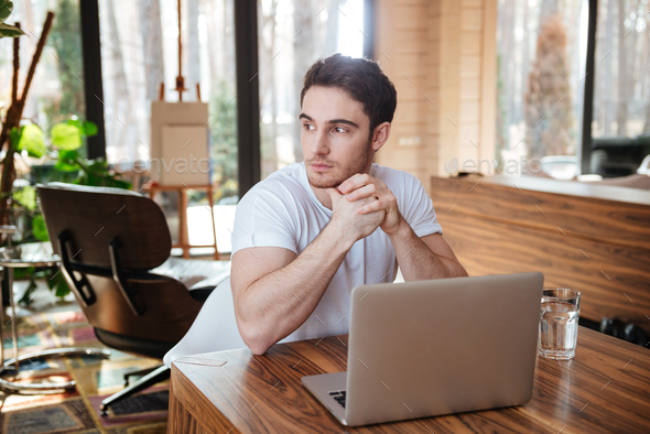 man with laptop looking away - Stock Photo - Images