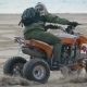 A Man Wearing a Helmet on His Head Performs an Extreme Trick on a Sports ATV on the Beach Area