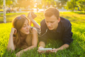 couple lying on grass with earphones and listening to music - PhotoDune Item for Sale