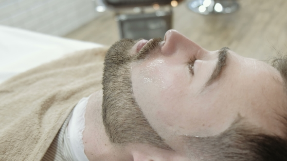 VideoHive Portrait of Handsome Young Man Getting Beard Shaving with Straight Razor Focus on the Blade 19919240