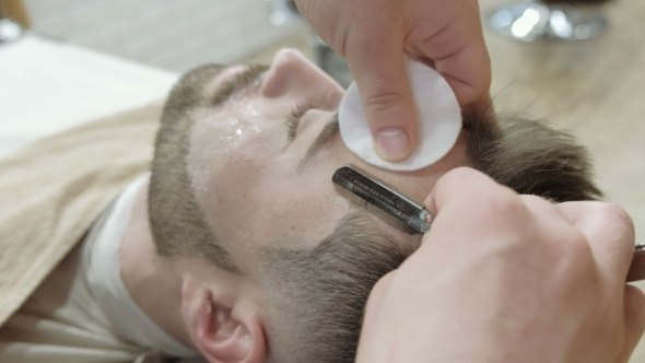 VideoHive Portrait of Handsome Young Man Getting Beard Shaving with Straight Razor Focus on the Blade 19919247