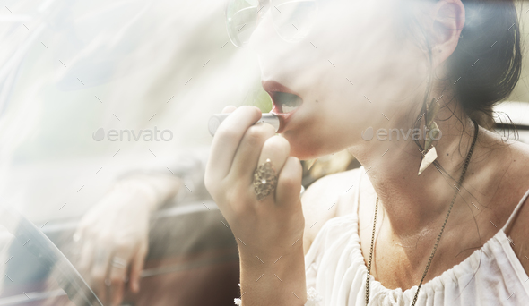 Woman Sitting in a Car Putting Lipstick on Lips with Rear Mirror - Stock Photo - Images