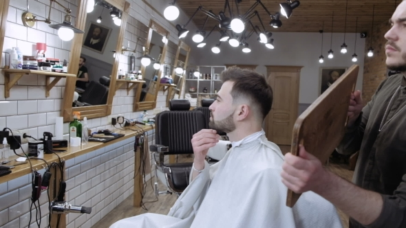 VideoHive The Barber Holds Up a Mirror and Shows Real Client Back in the Barbershop 19922819