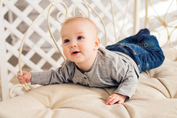 Adorable baby boy in sunny bedroom. Newborn child  - Stock Photo - Images