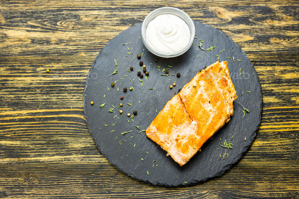 Grilled salmon steak with fresh lemon and sauce top view - Stock Photo - Images