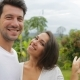 Couple Take Selfie Photo Embracing Outdoors Over Tropical Forest, Young Man And Woman Happy Smiling - VideoHive Item for Sale