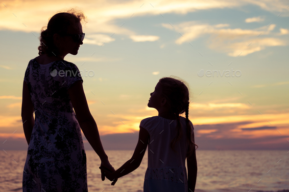 Mother and daughter playing on the beach at the sunset time. - Stock Photo - Images