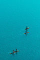 Aerial view of unrecognizable people stand up paddle boarding