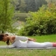 Young Woman Does Yoga Asana While Lying on Her Stomack at a River Bank - VideoHive Item for Sale