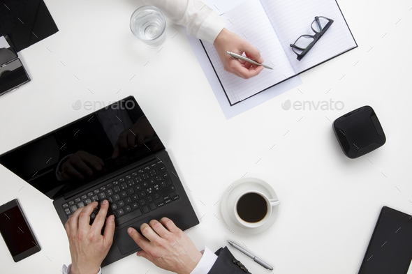 Businessman Using Laptop While Female Colleague Writing In Diary - Stock Photo - Images