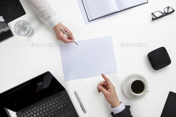 Business People Discussing Over Document At White Desk - Stock Photo - Images