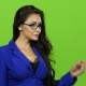 Woman in Glasses Flipping Through Virtual Slides. Green Screen Background
